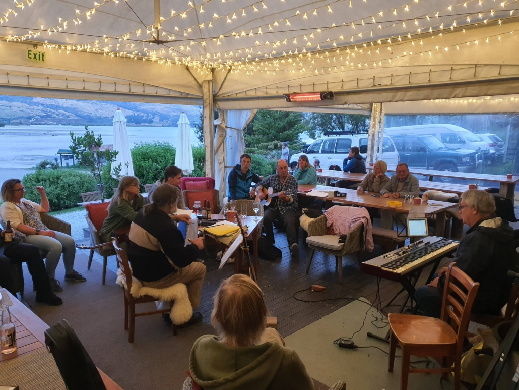 Small group of musicians and audience playing in restaurant marquee at dusk