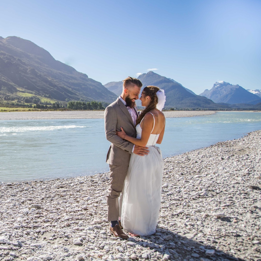Wedding couple cuddling in front of Dart River and mountains